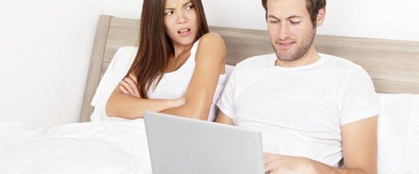 Cuplu modern în pat. El lucrează pe laptop și ea vrea atenție.